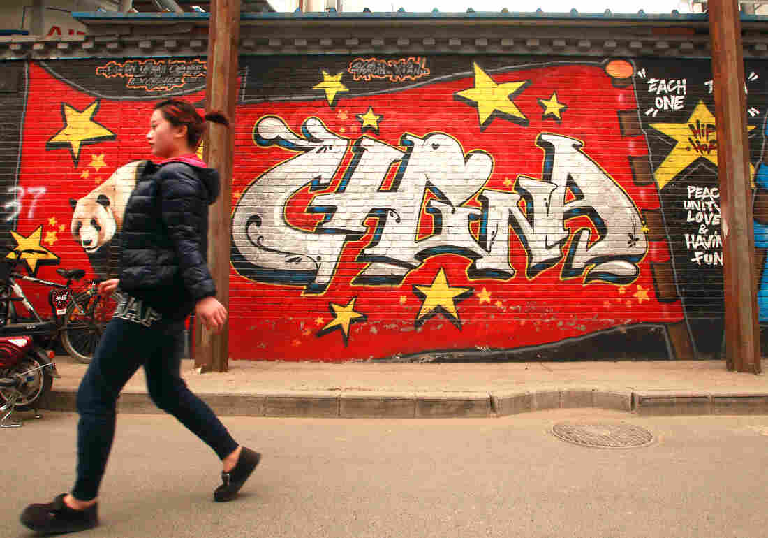 A woman in downtown Beijing walks past a building adorned with a patriotic mural by Chinese graffiti artists on April 22.
