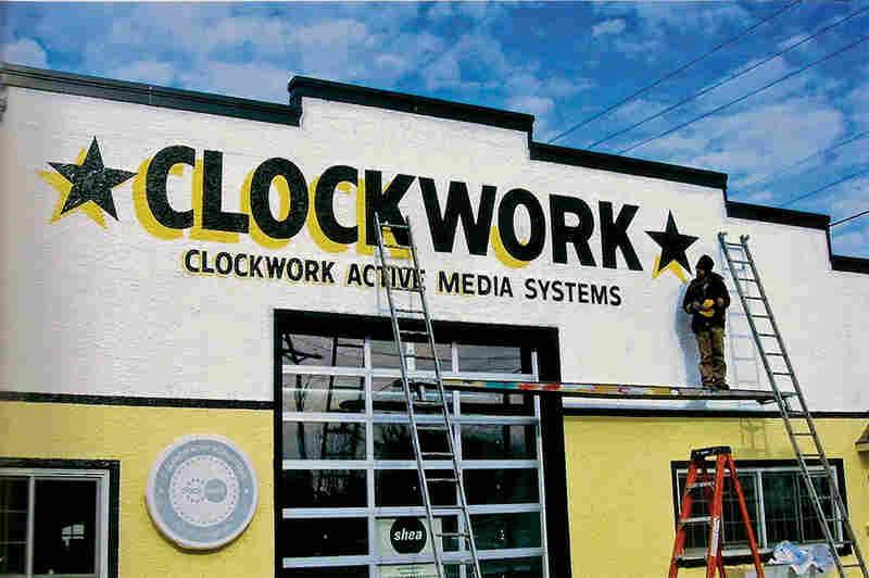 Phil Vandervaart paints the building of Clockwork Active Media Systems in Minneapolis.