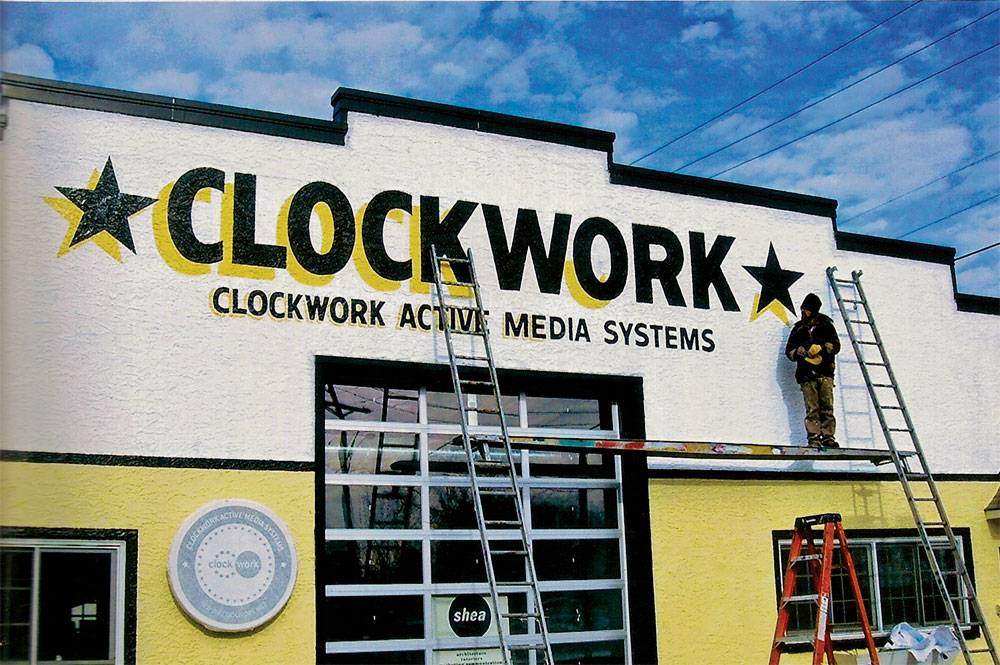 Phil Vandervaart paints the building of Clockwork Active Media Systems in Minneapolis.