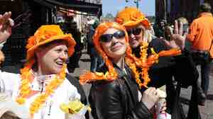 Tourists in Amsterdam wear orange Monday, one day before the investiture of the new Dutch king. Queen Beatrix, who ruled the Netherlands for 33 years, announced her abdication from the throne earlier this year.