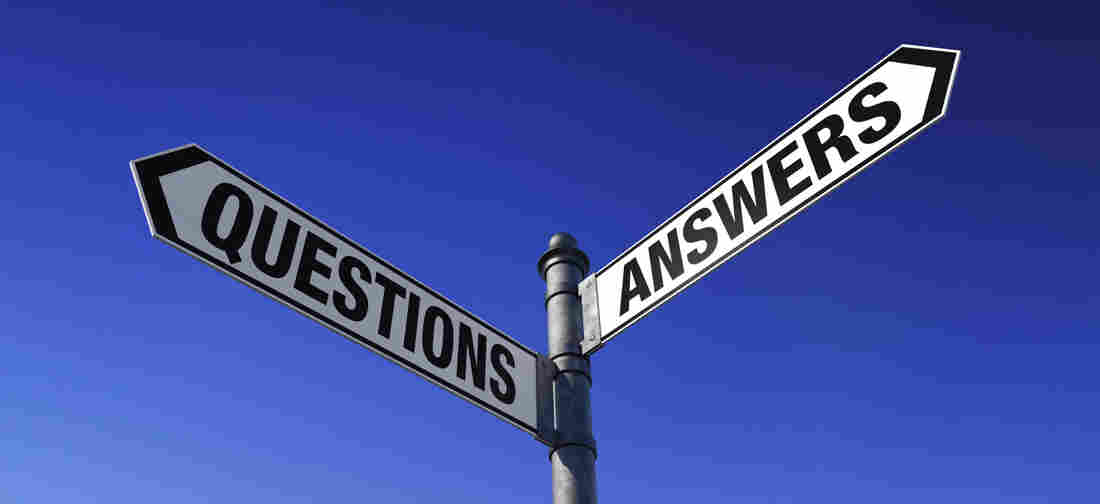 Street signs at an intersection. One says: questions. The other says: answers.