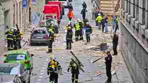Glass and other debris were  scattered across the street Monday after an explosion in Prague. Authorities initially suspected a gas leak. Dozens of people were injured in the Czech capital.
