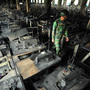 A Bangladeshi soldier walks through rows of burnt sewing machines Nov. 25, after a fire in the nine-story Tazreen factory in Savar, near Dhaka. The fire killed 112 people.