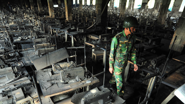A Bangladeshi soldier walks through rows of burnt sewing machines Nov. 25, after a fire in the nine-story Tazreen factory in Savar, near Dhaka. The fire killed 112 people. (AFP/Getty Images)