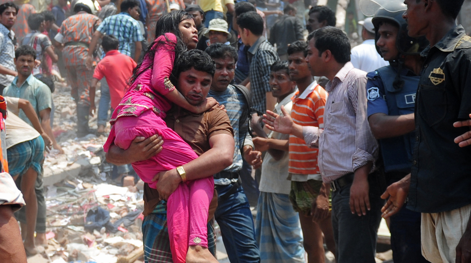 A  volunteer carries an injured garment worker after a building collapsed in Savar, on the outskirts of Dhaka, Bangladesh, on April 24, killing hundreds of people. (AFP/Getty Images)