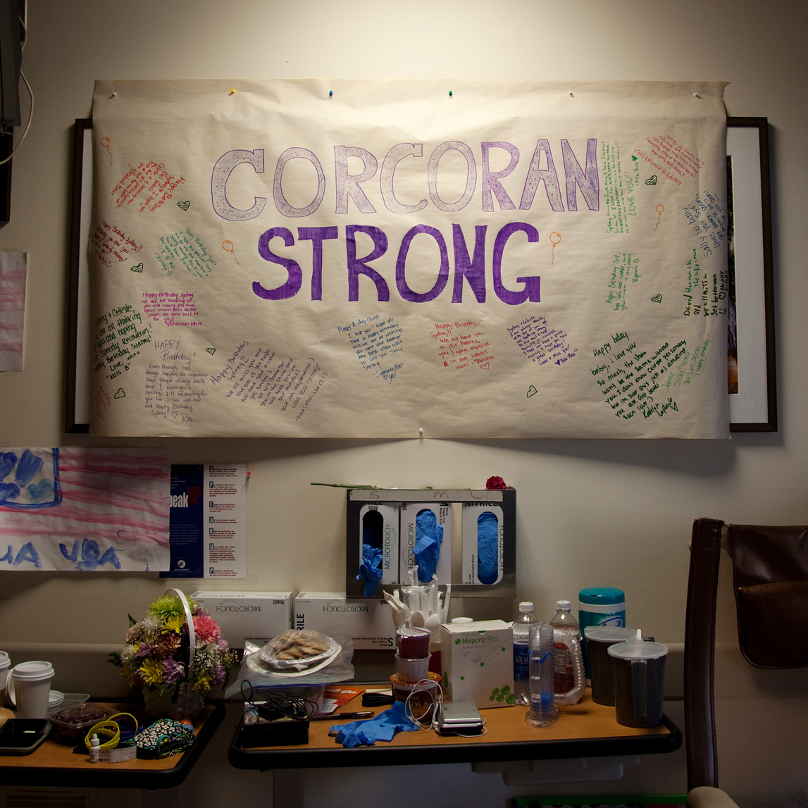 "A banner reading ""Corcoran Strong"" hangs on the wall of Celeste and Sydney's hospital room."