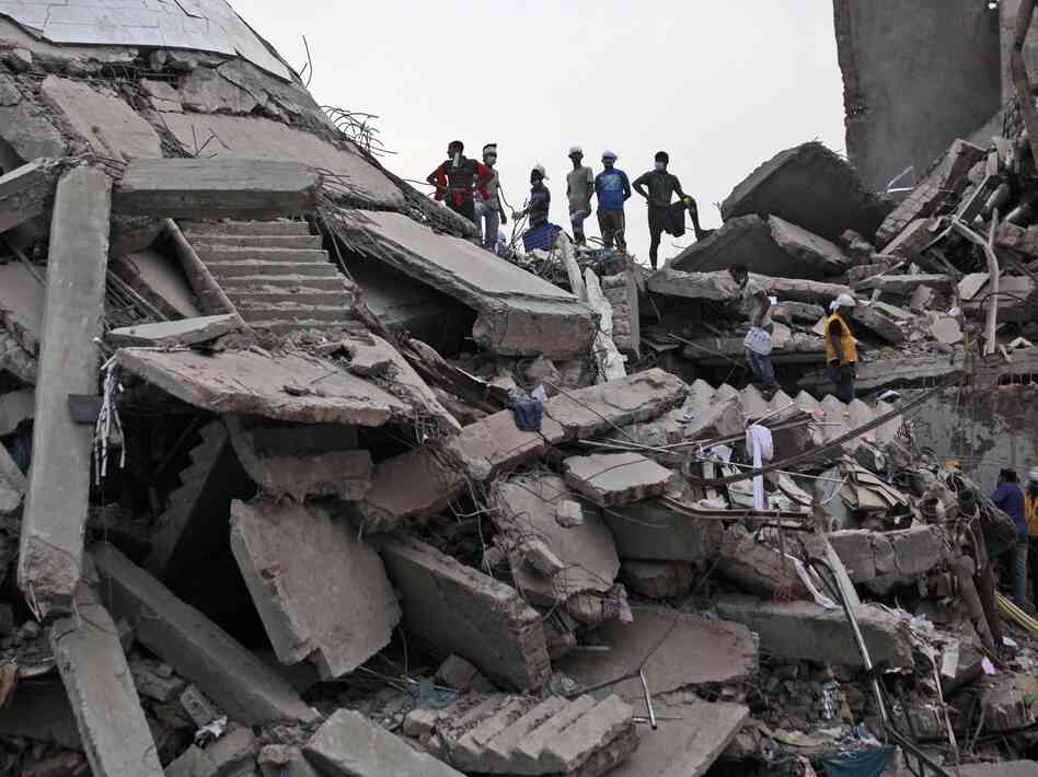 Bangladeshi rescue workers take a break Friday on the rubble of a building that collaps
