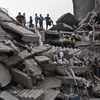 Bangladeshi rescue workers take a break Friday on the rubble of a building that collapsed Wednesday in Savar, near Dhaka, Bangladesh. By Friday, the death toll reached 300 as rescuers continued to search for injured and missing.