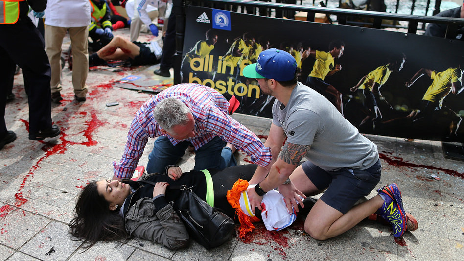 Bystanders help Sydney Corcoran at the scene of the first explosion near the finish line of the 117th Boston Marathon. (Boston Globe via Getty Images)