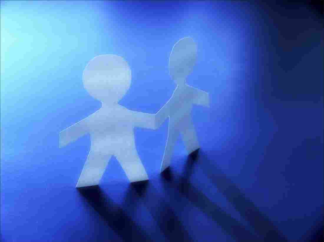 Paper cutouts of two figures holding hands on a blue background.