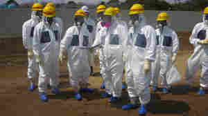 As they inspected an underground storage pool near the crippled Fukushima Daiichi nuclear power plant earlier this month, Tokyo Electric Power Co. President Naomi Hirose (4th from left) and other officials wore protective suits and masks. Radioactive water stored in some of the pits has leaked.