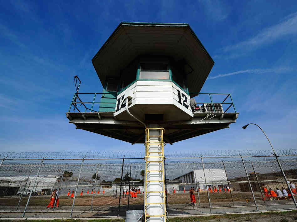 Inmates file by a guard tower at California's Chino State Priso