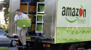 Amazon Fresh delivery man Tim Wilkie totes food to a house on Mercer Island, Wash.