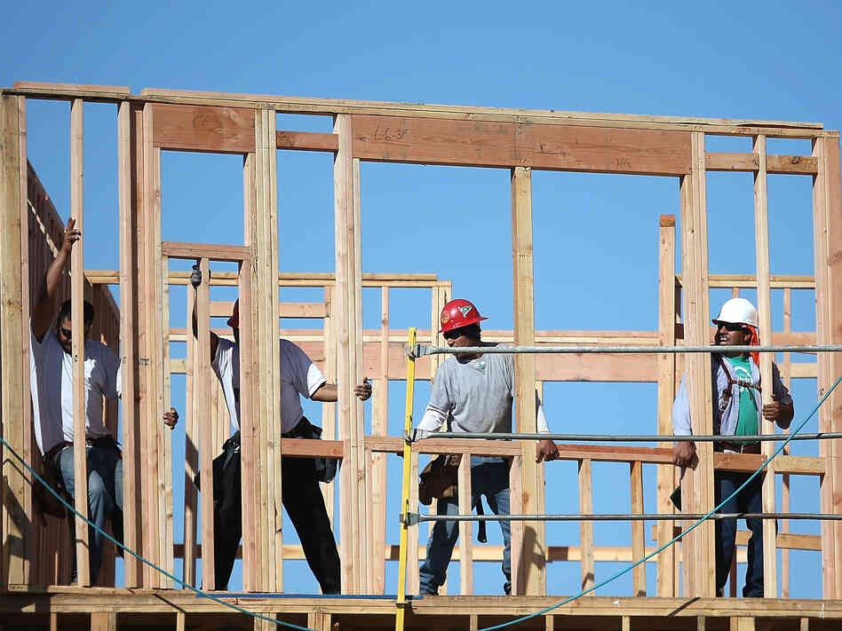 Construction workers move a framed wall into place at a new housing development in San Mateo,