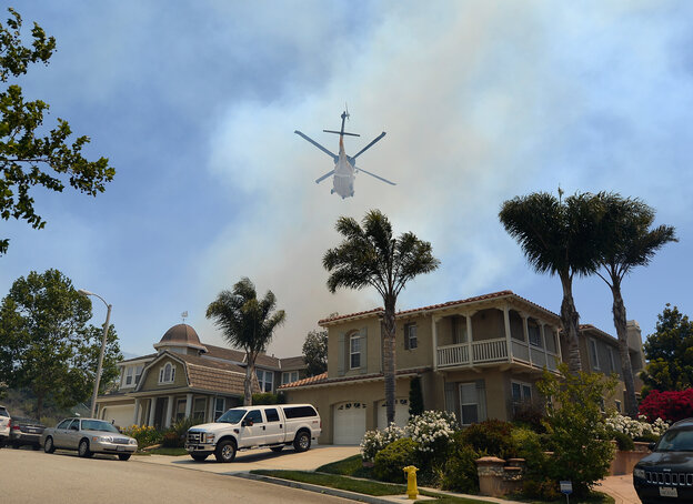 A fire fighting helicopter comes in to make a water drop behind some home threatened by a wildfire on Thursday in N
