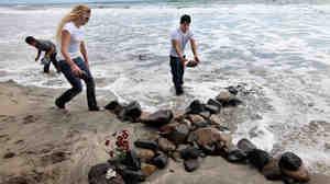 Adam Alvarado, Ashley Priest and Jimmy Garcia create a stone cross near the home of former NFL star Junior Seau's beach home i