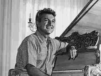 Liberace sits at a gold-leafed piano in the living room of his then-new Hollywood mansion in November 1961.