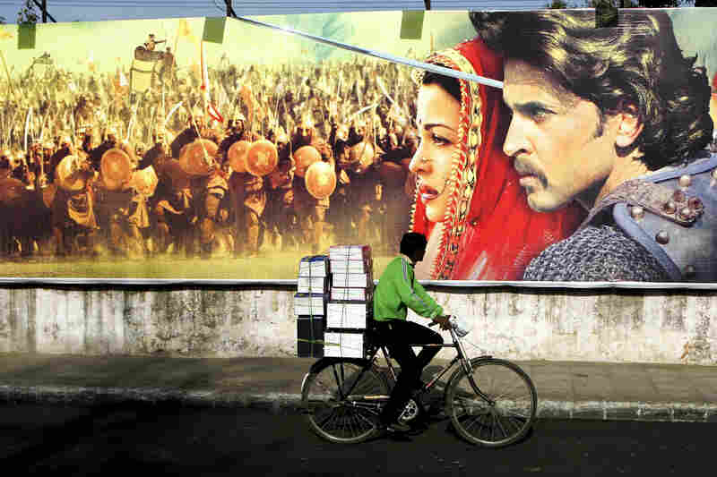 An Indian cyclist rides past an advertisement for the Bollywood film Jodhaa Akbar in New Delhi in 2008. The lavish film about the love between a Muslim emperor and his Hindu wife, played by actress Aishwarya Rai, opened in India to angry protests from members of the Rajput community, who said the historical romance was grossly inaccurate.