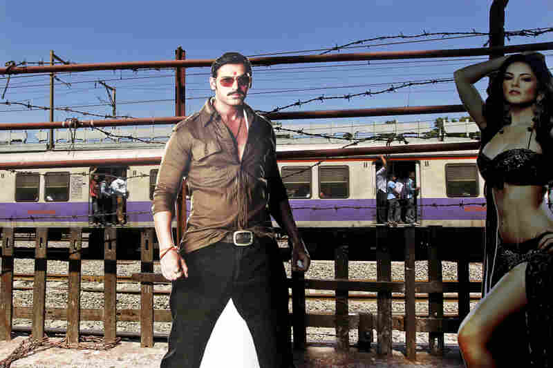 A train moves past a cutout of Bollywood actors John Abraham and Sunny Leone, outside a cinema hall in Mumbai. Four top Indian filmmakers have come together to make Bombay Talkies, a collection of short films that hits theaters on Friday.