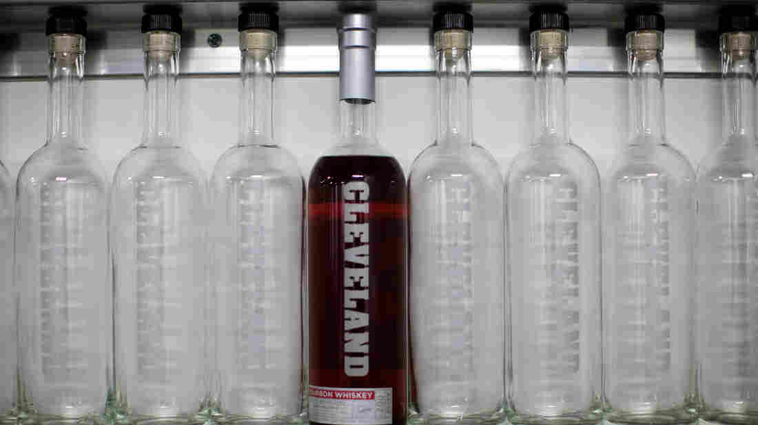 A bottle of Cleveland Whiskey's bourbon sits on a shelf with empty bottles at the company's distillery.