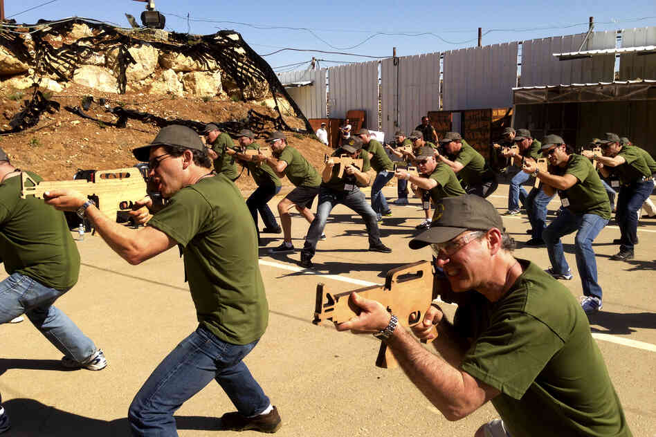 Businessmen from Philadelphia practice with wooden cutouts of rifles at Caliber 3, a counterterrorism training center in an Israeli settlement area south of Jerusalem. For a price, tourists interested in Israel's security can spend a few hours learning counterterrorism techniques.