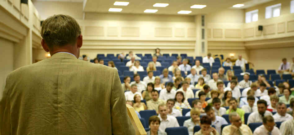 A man stands in front of a crowd in a lecture hall.