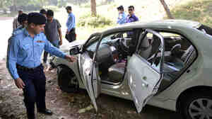 Pakistani police officials examine the bloodied, bullet-riddled car of slain government prosecutor Chaudhry Zulfiqar Ali after an attack by gunmen Friday in Islamabad.