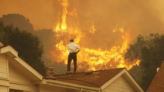 Standing on a rooftop, a man looks at the Springs fire's approaching flames in California Friday. The wildfire, reportedly, 20 percent contained, might be weakened by high humidity and cooler temperatures Saturday.