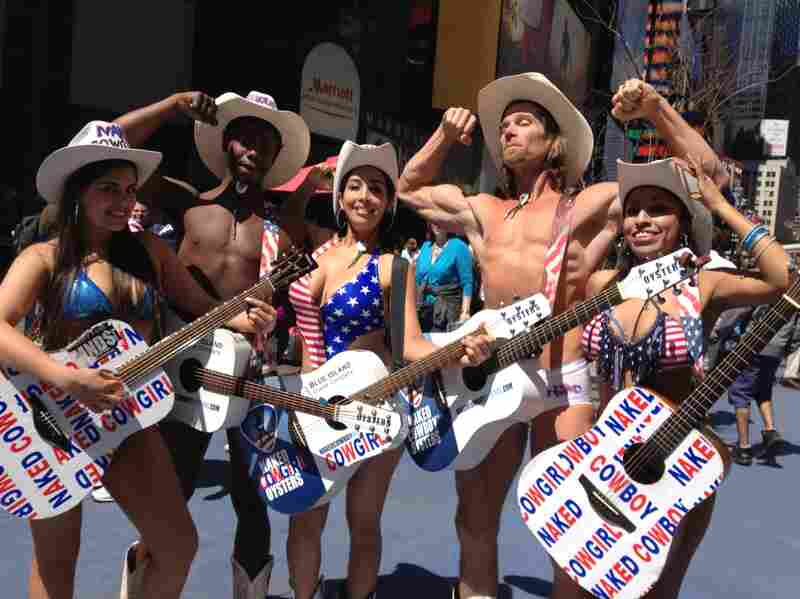 The original Naked Cowboy, Robert Burck (second from right), shows off with new naked cowfolk, from left, Karen Munos, Titus Gandy, Alejandra Quinones and Patricia Burck in New York's Times Square.