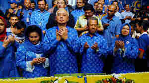 Malaysia's Prime Minister Najib Razak (second from left) celebrates his victory with a prayer on election day in Kuala Lumpur, Malaysia. His National Front coalition won a simple majority in the general election.