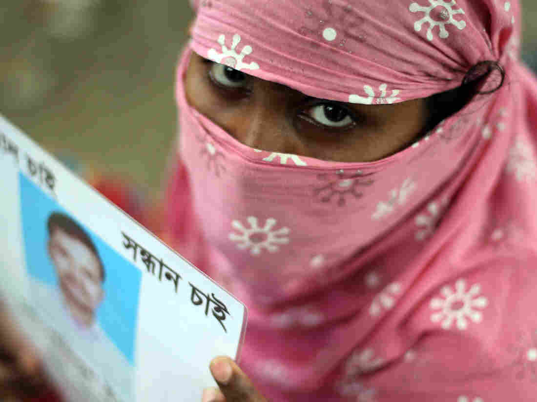 A Bangladeshi family member holds up the portrait of her missing relative, believed to be trapped in the rubble of the collapsed Rana Plaza.