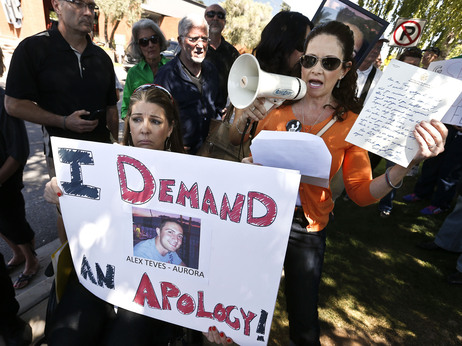 Caren Teves (right), whose son was killed in the Aurora, Colo., movie theater shooting, speaks as she holds up a letter from Sen. Jeff Flake, R-Ariz., during a rally outside Flake's Phoenix office April 19, just days after the gun vote.