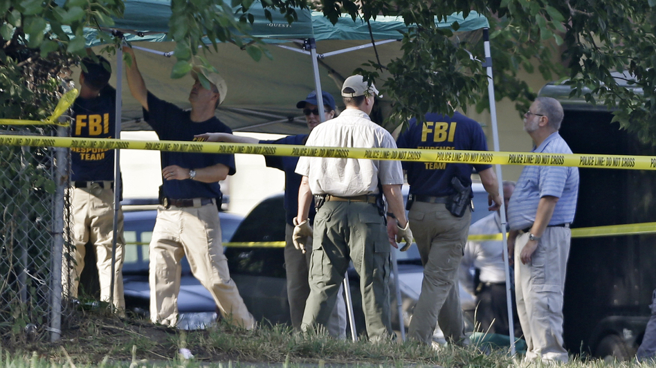 Cleveland police and FBI agents search a yard on the west side of Cleveland in July 2012 for evidence of Amanda Berry's disappearance. It turned out to be a false lead. (Associated Press)
