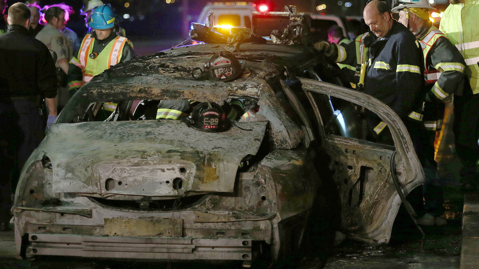 San Mateo County firefighters and California Highway Patrol officers investigate the scene of a limousine fire in which five women died Saturday.