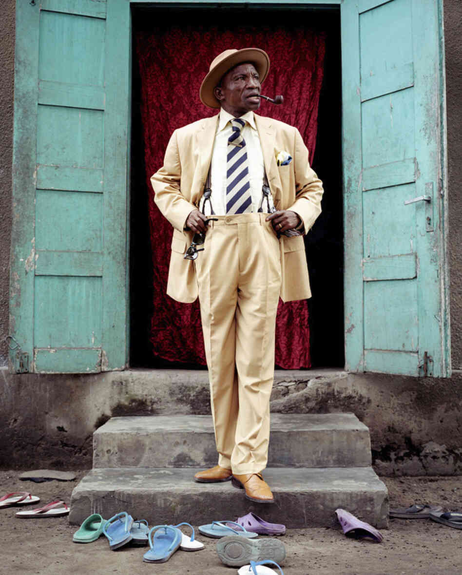 Severin Mouyengo, who has been a sapeur since the 1970s, poses in the entrance of his family house in the Bacongo neighborhood. Sandals on the ground are from his family members.