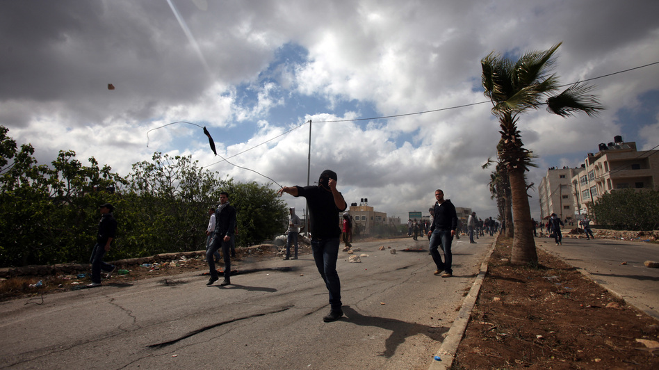 Palestinian youths hurl rocks at Israeli soldiers in Silwad on April 19, during clashes after a protest against the expropriation of Palestinian land by Israel. Last month, the Israeli prison authority said all of the Palestinian youths in prison for throwing rocks were boys.