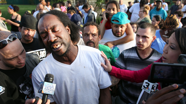 Charles Ramsey talks to media Tuesday as people congratulate him for having helped some women get out of a Cleveland home. Amanda Berry, Gina DeJesus, Michelle Knight and a 6-year-old girl were rescued from the house. (The Plain Dealer/Landov)