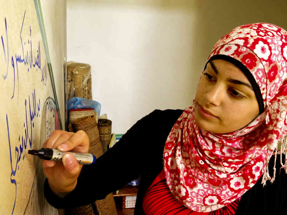 Yusra Hammed, 15, puts the finishing touches on a drawing on a wall inside her family's hom