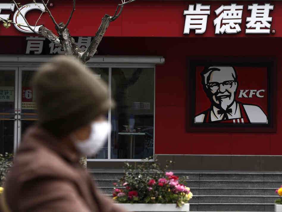 A woman wearing a mask rides past a KFC restaurant in Shanghai last month. Food scares and the
