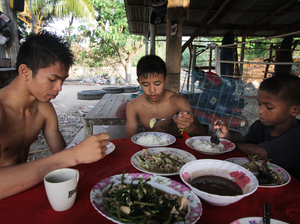 Chai (center) is shown at breakfast after his morning training with other fighters. He spends most of his day at the gym.