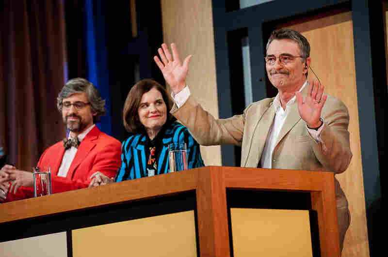 Panelist Tom Bodett (r) accepts approving applause from the audience after a well-placed zing. He's joined on state by humorists (l, c) Mo Rocca, Paula Poundstone.