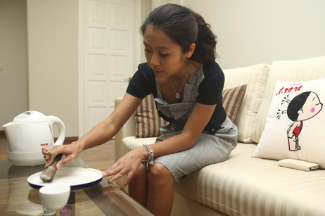 Nguyen Huong Giang, 24, grinds rhino horn with water at her apartment in Hanoi, Vietnam, in 2012. She ingests the liquid concoction after drinking too much alcohol or when suffering from allergies.