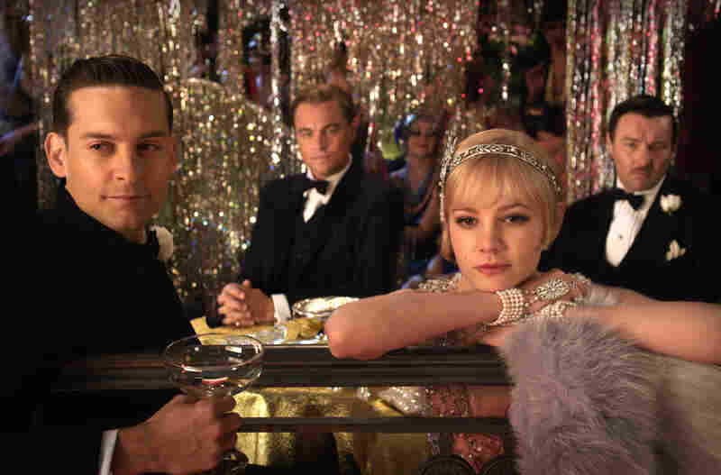 Under the watchful gaze of intrigued Midwesterner Nick Carraway (Tobey Maguire, left) and seething old-money scion Tom Buchanan (Joel Edgerton), Gatsby pays court to Tom's fascinated wife, Daisy (Carey Mulligan). Your local English major can tell you how that works out.