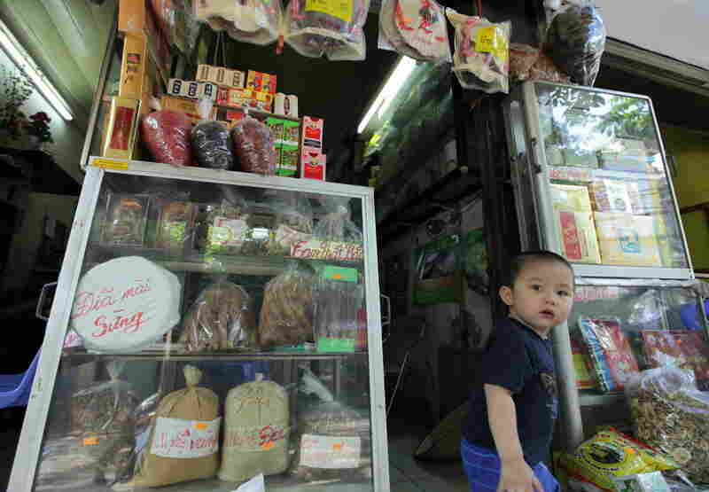 A young boy walks out of a traditional medicine shop in downtown Hanoi that sells grinding plates for rhino horns.