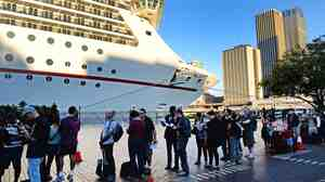Passengers queue at Sydney's Circular Quay to board the Carnival Spirit for a Pacific cruise, on Thursday.