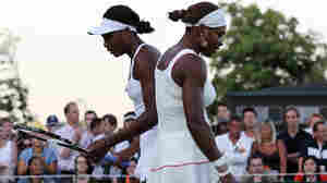 Serena Williams (left) and her sister Venus Williams in action during their first-round doubles match on Day 2 at Wimbledon in 2010.