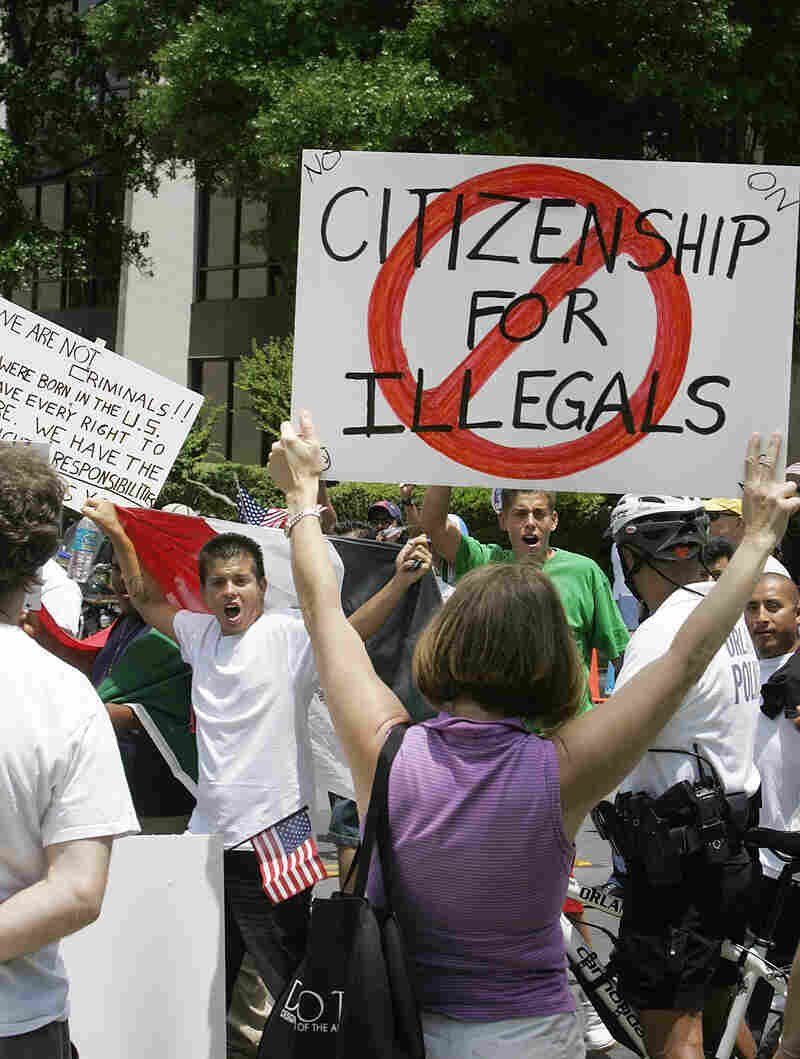 """Protesters demonstrate in downtown Orlando, Fla., on May 1, 2006. Most news outlets have long abandoned the use of the term """"illegals."""""""