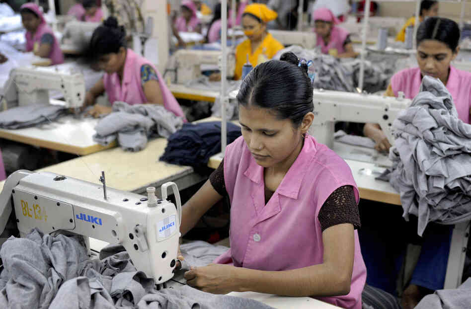 Garment workers sew T-shirts at a factory in Dhaka, Bangladesh, i