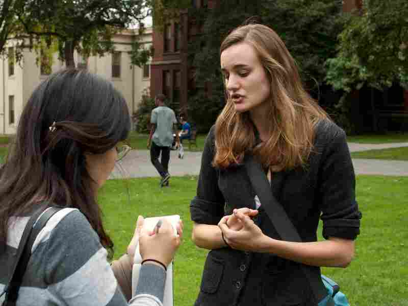 "Brown University senior Emily Kirkland (right) speaks with a student newspaper reporter. Kirkland, who studies environmental science, has been leading a divestment campaign at Brown and says she has seen how powerful such protests can be. ""Our administration is taking us very seriously,"" she says."