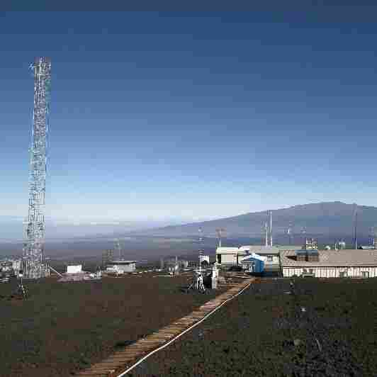 Researchers use the 120-foot tower atop Mauna Loa in Hawaii to collect air samples and measure the amount of carbon dioxide in the atmosphere. Mauna Kea looms in the distance.